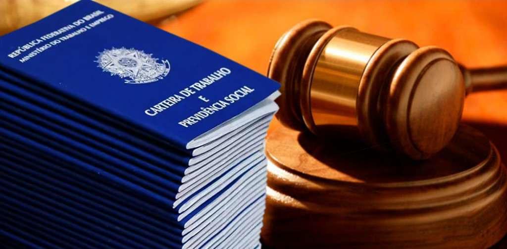 carteiras de trabalho empilhadas ao lado de um martelo de juiz